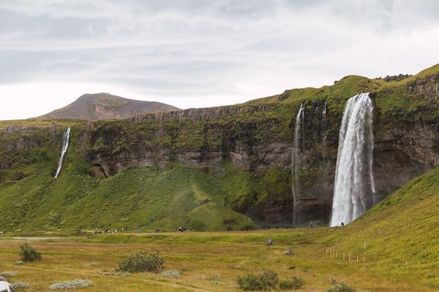 Sehr hoher und schöner wasserfall in island. traumhafter wasserfall in den grünen tälern der wunderschönen insel island