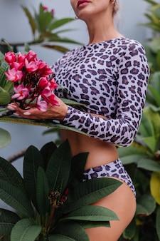 Sehr hübsche kaukasische frau mit perfektem körper im leopardenbadeanzug mit tropischen schönen blumen