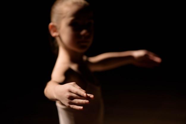 Sehr junge ballerina, die auf einem schwarzen hintergrund aufwirft