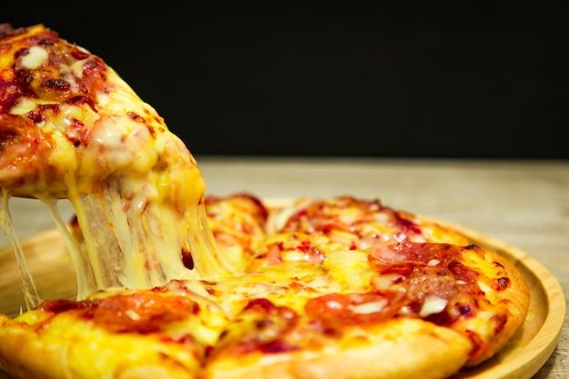 Sehr käsige pizzascheibe in der hand. heiße pizzascheibe mit schmelzendem käse