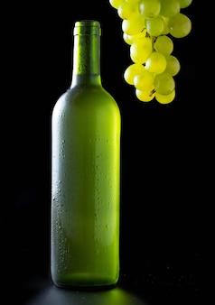 Sehr kalte weißweinflasche mit bündel weißen trauben auf schwarzem