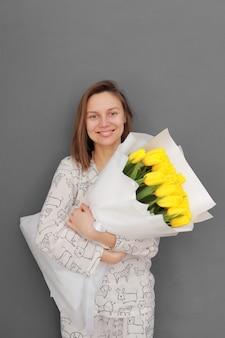 Sehr nette junge frau, die großen und schönen blühenden blumenstrauß der frischen gelben tulpenblumen auf dem grauen wandhintergrund hält
