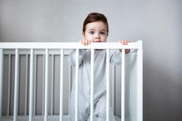 Sehr niedliches baby lächelt, das in der krippe in der weißen raumseitenansicht steht.