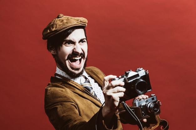 Sehr positiver fotograf, der im studio mit kameras aufwirft