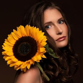 Sehr reizvolle frau zeigen ihren natürlichen blick mit einer sonnenblume