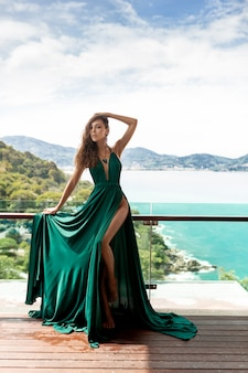 Sehr schöne dame mit schlanken beinen in einem langen grünen kleid, das balkon aufwirft. naturansicht - blaues meer und große grüne berge