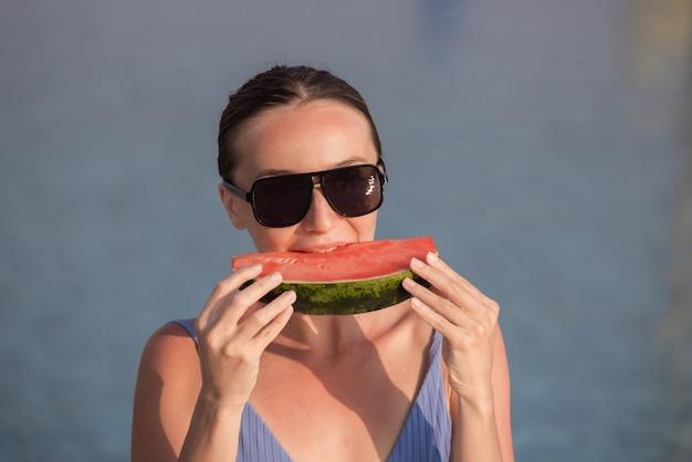 Sehr schöne frau mit wassermelone im pool