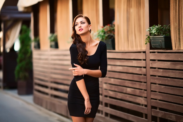 Sehr schöne junge brunettefrau, die in der straße trägt