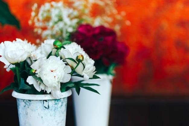 Sehr schöne pions in den vasen, die auf tabelle, geschenk für frau stehen