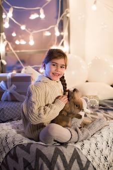 Sehr schöne und charmante kleine dunkelhaarige frau in weißem pullover hält ein lebendes kaninchen