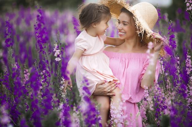 Sehr schönes bild der jungen mutter und des kindes im blumenfeld