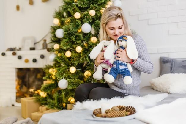 Sehr schönes und charmantes mädchen im weißen pullover hält ein lebendes kaninchen im inneren des hauses. neujahr. weihnachten. hase.