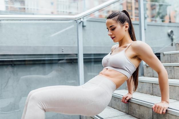 Sehr sexy, fit athletische frau trainiert ihren oberkörper während eines bootcamp-trainings.