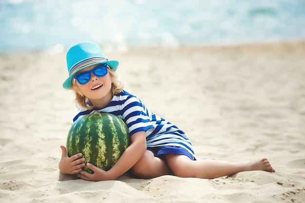 Sehr süß fröhliches kind mit wassermelonen am meer. lächelnder junge auf dem strand, der spaß auf dem sand nahe dem wasser hat