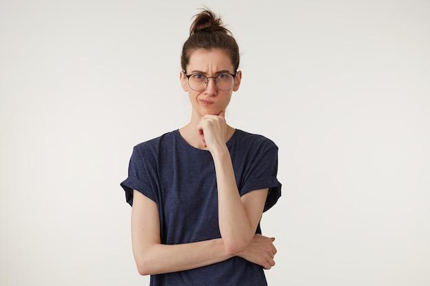 Sehr unzufriedene junge lehrerin sieht ihren schüler skeptisch an, der eine faust unter dem kinn hält