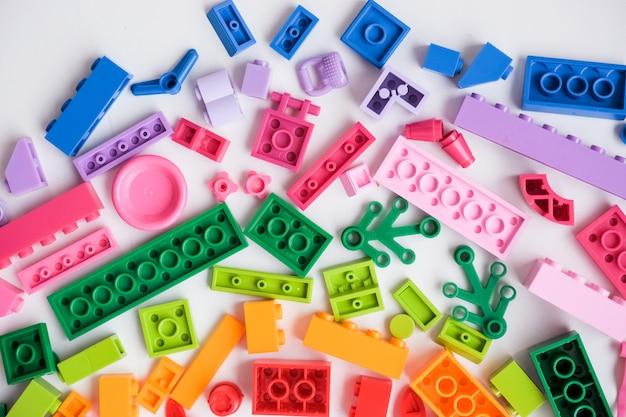 Sehr viele kinderspielzeuge. flach liegend. spiel für die kindertagesstätte, vorschule. kindergarten-lernspiele. die farben des regenbogens. bunte plastikspielwaren in der verschiedenen form.