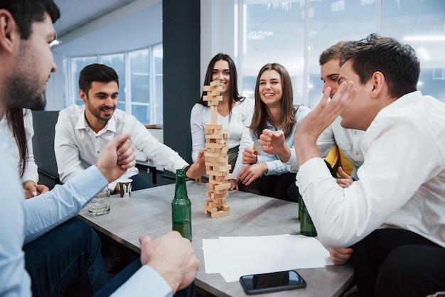 Sei bitte vorsichtig. erfolgreiches geschäft feiern. junge büroangestellte sitzen in der nähe des tisches mit alkohol
