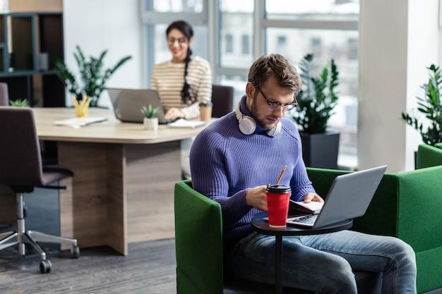 Sei ernst. aufmerksame bärtige männliche person, die kopf neigt, während nachrichten online lesen