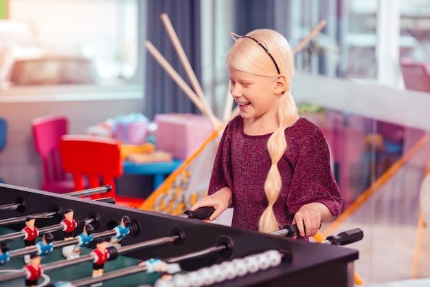 Sei glücklich. charmantes blondes mädchen, das lächeln auf ihrem gesicht hält, während das wochenende im spielzentrum verbringt