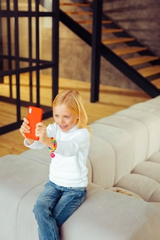 Sei glücklich. fröhliches mädchen, das beim spielen mit telefon ein lächeln auf dem gesicht behält