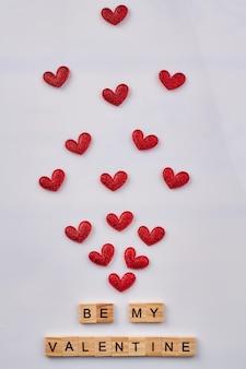 Sei mein valentinstag aus holzwürfeln. rote herzen des vertikalen schusses auf weiß.