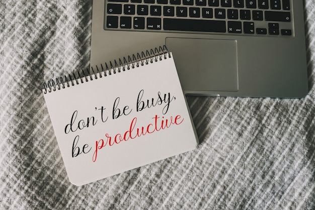 Sei nicht beschäftigt, sei ein produktives motivationszitat, das auf ein papier im notizbuch geschrieben ist