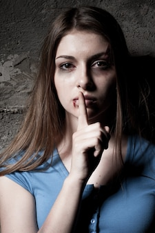 Sei nicht ruhig! junge verprügelte frau, die in die kamera schaut und den finger auf den mund hält, während sie gegen eine dunkle wand steht?