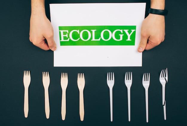 Sei plastikfrei. kein verlust. hände halten papier mit wort ökologie in der nähe von umweltfreundlichen natur- und einweggabeln. gabeln sind in der reihe auf dunklem hintergrund, draufsicht. reduzieren sie die wiederverwendung.