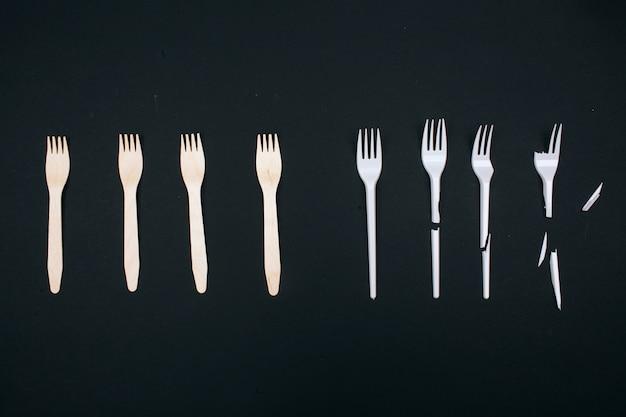 Sei plastikfrei. kein verlust. umweltfreundliche, ungebrochene und zum einmalgebrauch kaputte gabeln in der reihe, draufsicht. wählen sie einwegkunststoff oder ein wiederverwendbares recycelbares produkt. plastikverschmutzung