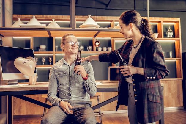Sei positiv. hübsche männliche person, die an seinem arbeitsplatz sitzt, während bier trinkt