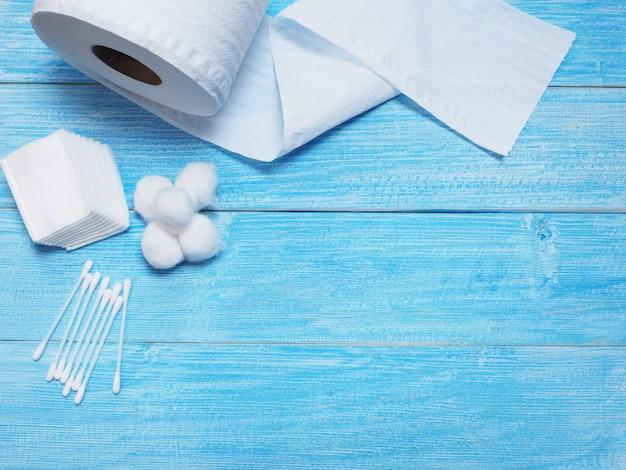 Seidenpapier und wattestäbchen auf hölzernem blauem hintergrund.