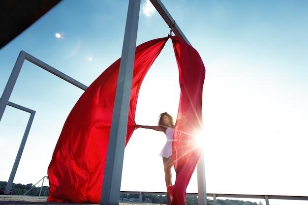 Seidentänzer des schönen brunette mit den roten vorhängen, die an der dachspitze aufwerfen