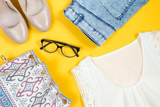 Seidenweißes oberteil, jeansshorts, nackte schuhe, geldbörse, schwarze brille auf hellem hintergrund