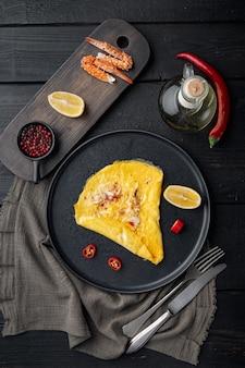 Seidiges omelett der chili-krabbe, auf teller, auf schwarzem holztischhintergrund, draufsicht flach gelegt