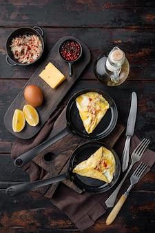 Seidiges omelett mit chilikrabben, auf bratpfanne, auf dunklem holzhintergrund, draufsicht flach liegen