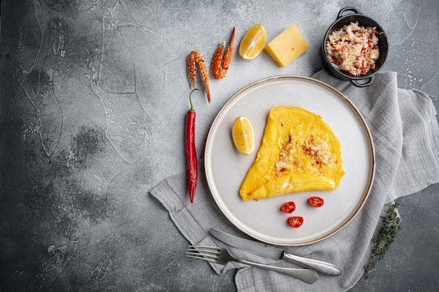 Seidiges omelett mit chilikrabben, auf teller, auf grauem hintergrund, draufsicht flach, mit copyspace und platz für text