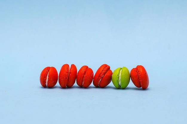 Seien sie ein anderes konzeptfoto aus der reihe von macarons mit grünem macaron zwischen roten macarons