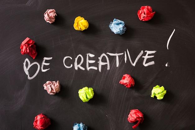 Seien sie kreativitätswort mit buntem zerknittertem papierball auf tafel