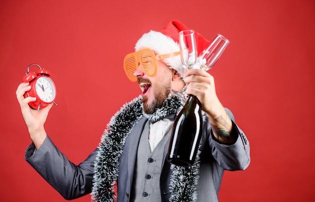 Seien sie nicht zu spät. frohes neues jahr. geschäftsmann weihnachtsmütze mit lametta und uhr. weihnachten macht spaß. mann geschäft champagner aus gläsern trinken. zeit für winterferien. mann feiert weihnachtsfeier.
