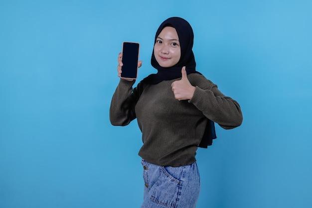 Seien sie schlau, kaufen sie dieses gerät, das porträt einer jungen asiatischen frau, die laut lacht, einen hijab trägt, der auf das smartphone zeigt und den gerätebildschirm zeigt