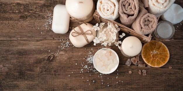 Seife, salz, handtücher und kerzen auf einem braunen hölzernen hintergrund. oben