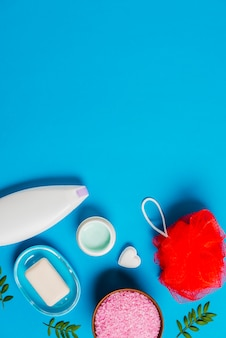 Seife; schwamm; sahne und rosa salz auf blauem hintergrund