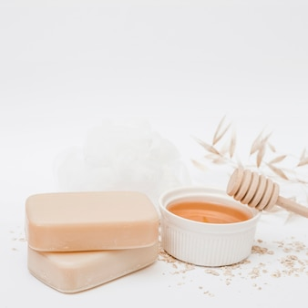 Seifen; honig; honigschöpflöffel und luffa auf weißer oberfläche