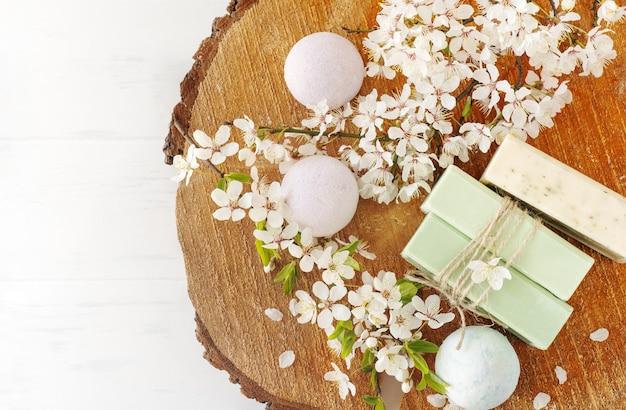 Seifenbanner. aromatische naturseife und badebombe mit sakura-blüten auf holzhintergrund, ansicht von oben