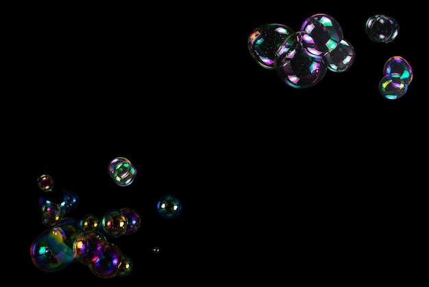 Seifenblasen auf einer schwarzen oberfläche isoliert. platz kopieren.