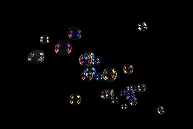 Seifenblasen auf schwarzem hintergrund isoliert. platz kopieren.