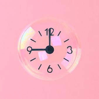 Seifenblasen mit pfeilen in form einer uhr auf einem rosa pastellhintergrund. minimalismus.