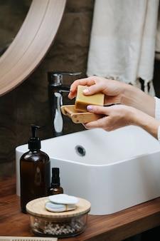 Seifenschale aus holz in den händen einer reifen frau mit einem öko-seifenblock. sie steht in einem badezimmer vor dem waschbecken.