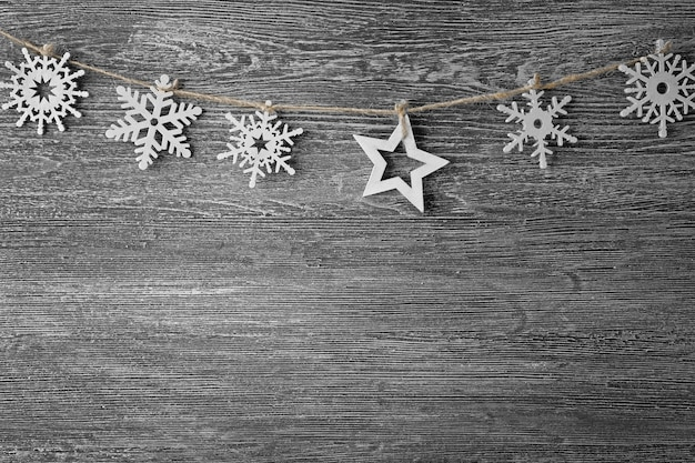 Seil mit schneeflocken und stern auf grauem holzhintergrund