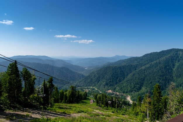 Seilbahn sessellift in den bergen. mit dem lift den berg besteigen. schöne aussicht von der spitze des berges auf die hügel mit nadelwald bedeckt.